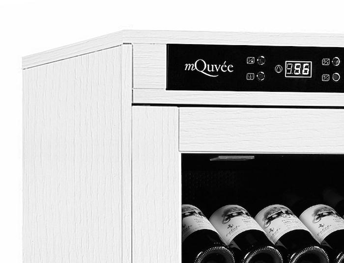 Liten del av displayen från ett vitt vinlagringsskåp i trä från mQuvée
