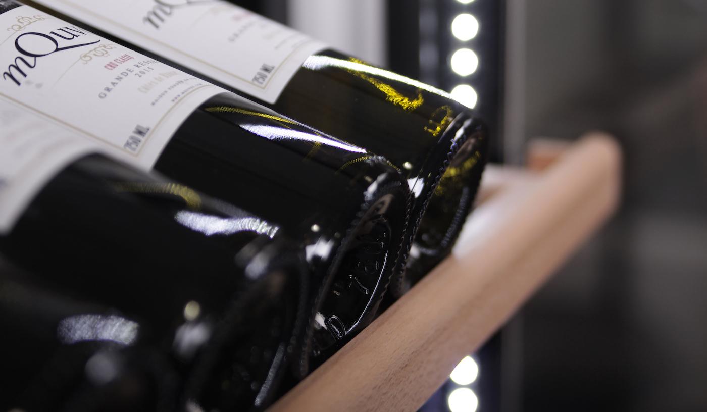 Svart vinlagringsskåp - detaljbild på hylla med vinflaskor