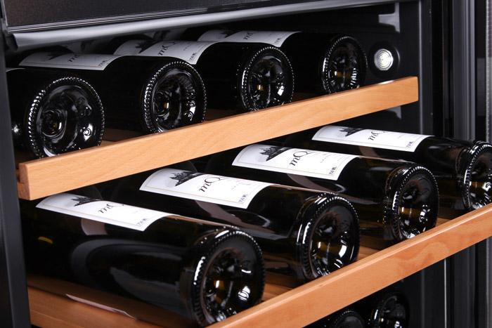 Inbyggbar vit vinkyl med 3 vinflaskor på utdragen hylla